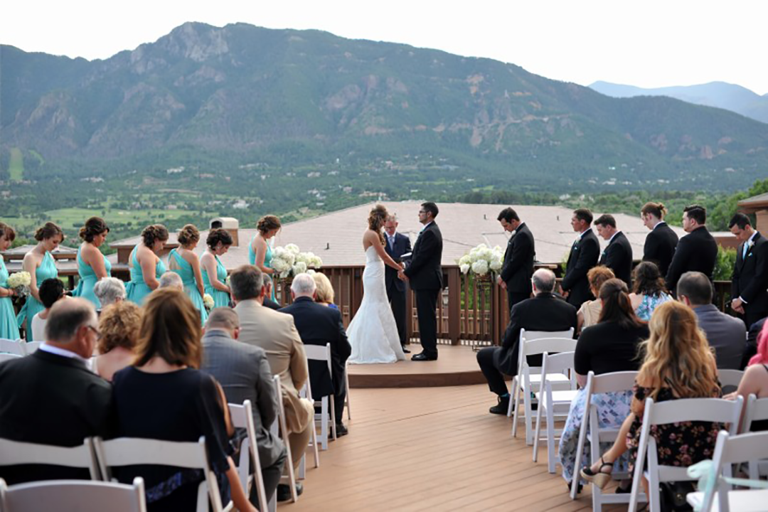 bride and groom at wedding ceremony in front of lake and mountain