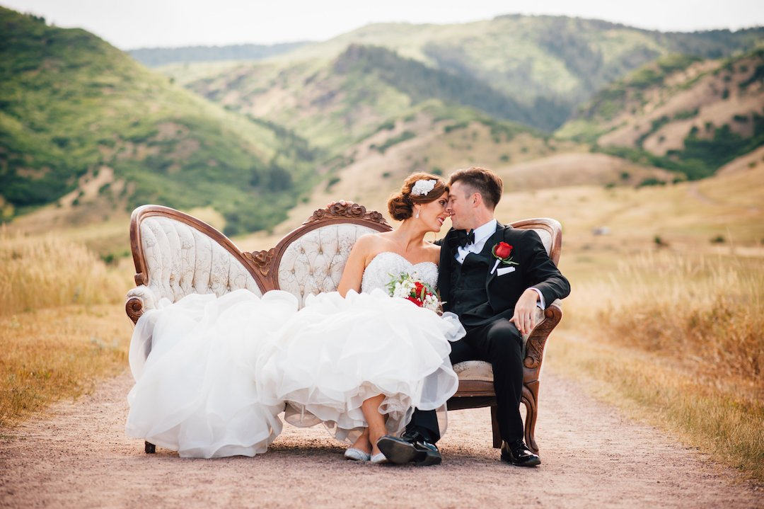 bride and groom sitting on vintage couch