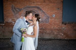 bride and groom kiss in front of brick wall