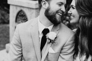 black and white groom smiling at bride