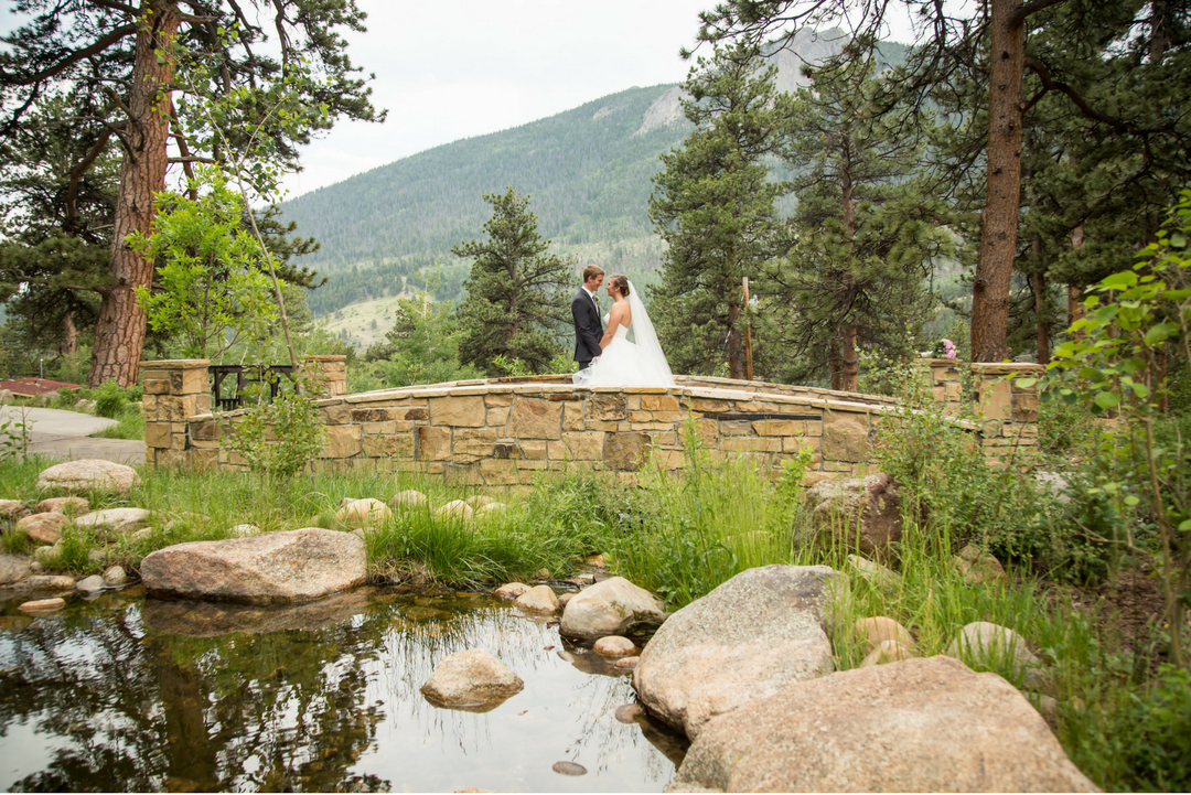 bride and groom on bridge in mountains