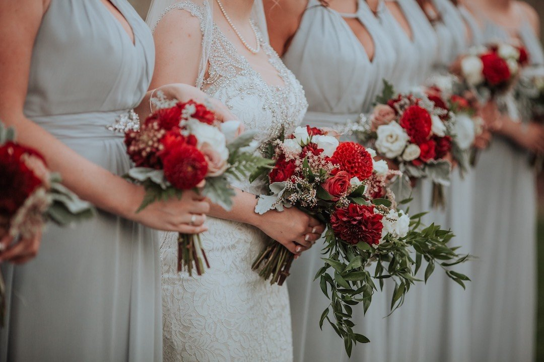 bridesmaids holding red and white wedding bouquets