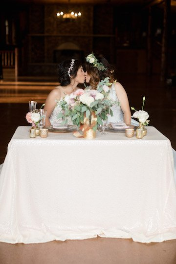 brides kissing at sweetheart table